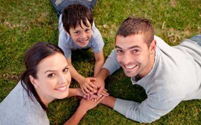 parents and child laying on grass with hands together